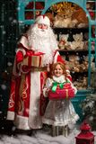 Father Frost and Snow Maiden standing with gifts. Russian Christmas characters Ded Moroz Father Frost and Snegurochka Snow Maiden standing with gifts Royalty Free Stock Images