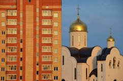 A Russian church and a Soviet block of flats Royalty Free Stock Photo
