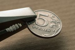 The Russian coin in the iron grip. Of sanctions Stock Photography