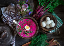 Russian cold soup with beetroot, bowl,spoons,greenery on dark wooden table. Style rustic. Royalty Free Stock Image