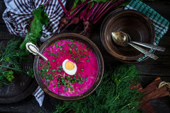Russian cold soup with beetroot, bowl,spoons,greenery on dark wooden table. Style rustic. Royalty Free Stock Images