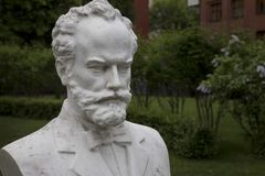 Russian composer Pyotr Ilyich Tchaikovsky. The bust of the Russian composer Piotr Ilyich Tchaikovsky is set in front of the open stage in the Hermitage Garden in royalty free stock image