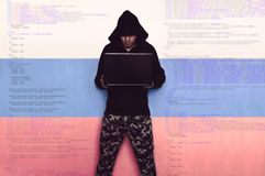 Russian computer troops. Information war. A hacker in military uniform with a black hood, with a laptop on the background of Russian flag and the code. Russian Stock Photos