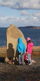 Russian Convoy Memorial with two kids reading inscription. Gairloch Highlands, Scotland. Russian Convoy Memorial with two kids reading inscription. Sadness shown Stock Image