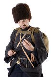 Russian Cossack inspecting a poniard. Young man is wearing vintage uniform of Russian foot Cossack in time First World War. Re-enactor is looking over a dagger Stock Photography