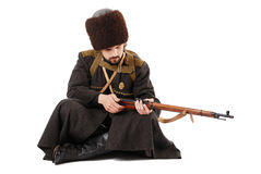 Russian Cossack inspecting a rifle. Young man is wearing vintage uniform of Russian foot Cossack in time First World War. Re-enactor is sitting and looking over Royalty Free Stock Photo