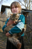 Russian countryside girl 8 years old, holds big shaggy cat. Stock Photo