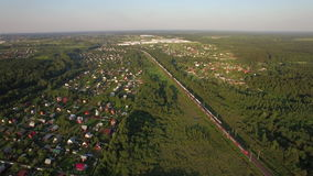 Russian countryside and railway, aerial view. Aerial shot of Russian countryside with village, green woods and trains running there stock video footage