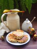 Russian cuisine : crepes pancakes on plate with oak flakes on  brown wooden background with rustic milk jug, honey and traditional stock photography