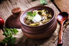 Russian cuisine: Solyanka - Soup from different kinds of meat an. D vegetables in a clay pot. Vintage wooden background, selective focus royalty free stock photography