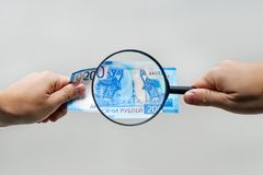 Russian currency, including new 2000 rouble bills. men's hands hold 2000 rubles and a magnifying glass. verification of the. Authenticity of the Russian royalty free stock images