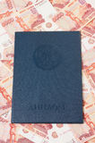 Russian diploma against money. Russian diploma of higher education on money background stock images