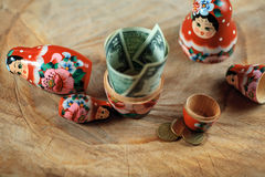 Russian doll with dollars inside. Anti crisis money box. Matrioska bank. Stock Photo