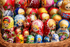Russian doll Matryoshka family. Unique wooden Russian Matryoshka dolls in different color shades in a wicker basket like one big family Stock Images