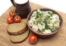 Russian dumplings, bread and cherry tomatoes on a cutting board Stock Photo