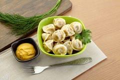 Russian dumplings - pelmeni, in green bowl. Food Royalty Free Stock Photo