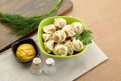 Russian dumplings - pelmeni, in green bowl. *with mustard Stock Photo
