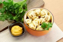 Russian dumplings - pelmeni,  *with mustard. Russian dumplings - pelmeni, in orange bowl *with mustard Stock Image