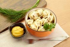 Russian dumplings - pelmeni,  *with mustard. Russian dumplings - pelmeni, in orange bowl *with mustard Royalty Free Stock Photos