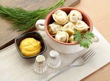 Russian dumplings - pelmeni, in orange bowl *with mustard. Food Stock Photos