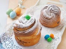 Russian easter cake, kulich. Cruffin dessert decorated with sugar powder and easter eggs. Homemade treat. Stock Photo