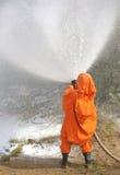 Russian Emergency Control fireman in orange uniform extinguishin Stock Photos