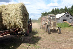 Russian Farm tractor moves round bales of hay near barn. Royalty Free Stock Images