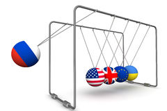 The Russian Federation as a factor in the dynamics of geopolitics. The concept. Newton`s Cradle with the image of the Russia flag, USA, Great Britain, the Royalty Free Stock Image