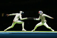 Russian fencer (L) attacks Great Britain fencer at the Men's team foil quarterfinal of the Rio 2016 Olympic Games. RIO DE JANEIRO, BRAZIL - AUGUST 12, 2016 stock photography