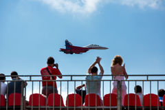 Russian fighter aircraft and spectators in the stands Royalty Free Stock Photo