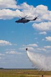 Russian firefighting helicopter with waterbag on fire extinguishing training royalty free stock image