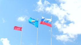 Russian flag and Astrakhan region flag waving in. The wind over blue sky stock video footage