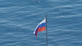 Russian flag on the sea in the Crimea. Flag fluttering against blue water background. Russian flag on the background of the sea. Russian tricolor on a stock footage