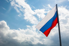 Russian flag on the beautiful sky. Russian flag on the background of the beautiful sky stock photo