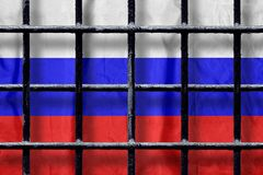 Russian flag behind black metal prison bars with shadows. Russian flag behind black metal bars of a prison grate with shadows. Symbol of oppression of freedom in royalty free stock images