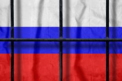 Russian flag behind black metal prison bars with shadows. Russian flag behind black metal bars of a prison grate with shadows. Symbol of oppression of freedom in royalty free stock photo