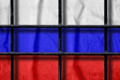 Russian flag behind black metal prison bars with shadows. Russian flag behind black metal bars of a prison grate with shadows. Symbol of oppression of freedom in stock images