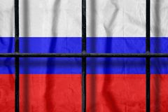 Russian flag behind black metal prison bars with shadows. Russian flag behind black metal bars of a prison grate with shadows. Symbol of oppression of freedom in stock photo