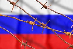 Russian flag behind rusty barbed wires with shadows. Symbol of violation of human rights in Russia stock image