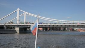 Russian flag on boat moving away from Krymsky Bridge stock video footage