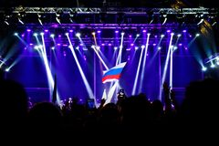 Russian flag at the concert, opposite the light from the stage. Russian flag at the concert, opposite the light from the stage Royalty Free Stock Photos