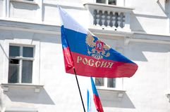 The Russian flag developing on the wind. Against the background of the old white house Royalty Free Stock Photos