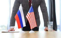 Russian flag and flag of European Union with businessman near by. Stock Photo