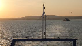 Russian flag fluttering in the wind on the stern of the ship. View from ferry sails through the Strait of Kerch from Crimea to Russia at sunset. seascape with stock footage