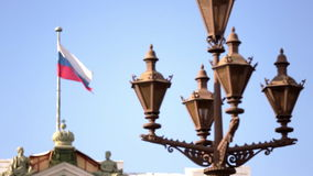 Russian flag flutters in the wind on the flagpole on blue sky background. Flag of the Russian Federation develops on the wind on the roof of the building on stock video footage