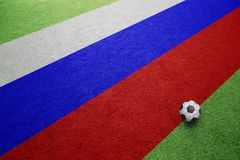 Russian flag on football field with soccer ball. Russia flag on sunny football grass field with ball. Copy space background Royalty Free Stock Photos