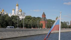 Russian flag in front of Kremlin walls, towers and churches. Russian flag on boat in front of red brick Kremlin walls, towers and white churches with golden stock footage