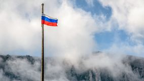 Russian flag overlooking Mount Ai-Petri in Crimea. Russia. Waving Russian flag on the cloudy blue sky background royalty free stock image