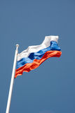 Russian flag on a pole against blue sky Royalty Free Stock Photos