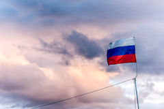 Russian flag on the rain clouds background stock photo